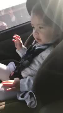 Bimba che balla sul seggiolino in auto con la musica alla radio